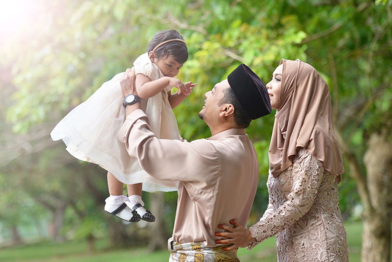 Kind Muslim parents playing with child, inspired by Prophet Muhammad
