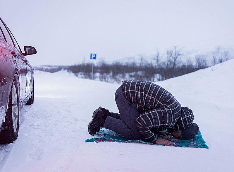 Muslim man traveller praying on snow
