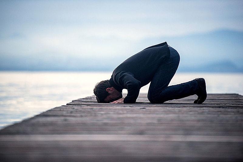 Muslim man praying on a wooden pier in dusk