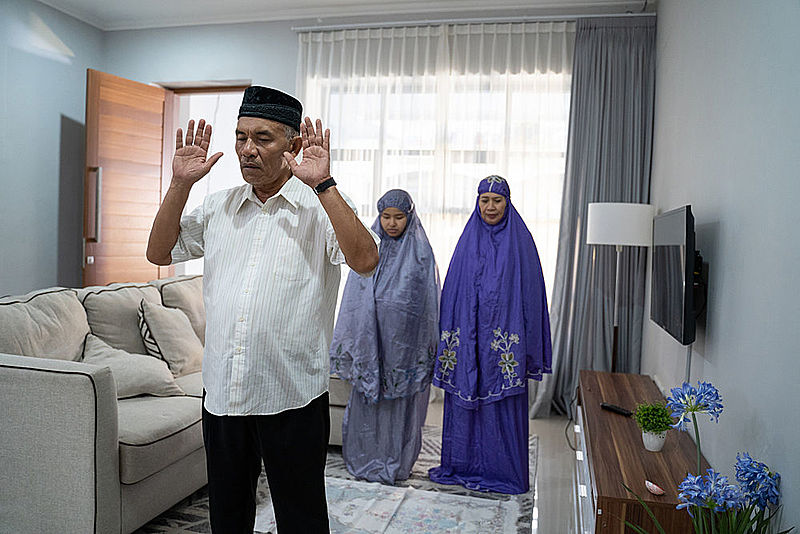 Elderly father leading Muslim congregational prayer